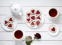 Heart shaped cookies for Valentines day with teapot and two cups of tea and rose composition on white wooden background. Baked handmade shortbread delicious snack. Romantic meal for couple. Food concept of love. Top view, flat lay.