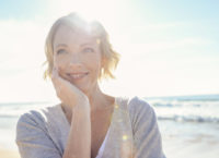 Beautiful mature woman portrait on the beach. She is happy and smiling with the sun and sea behind her. She looks relaxed and could be on vacation.